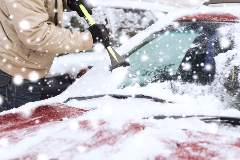 Scraping ice off snowy windshield.