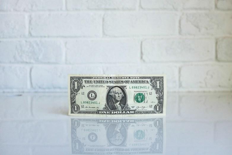 One dollar bill in front of brick