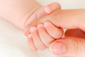 8092918 - close-up of baby's hand holding mother's finger