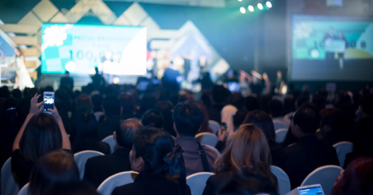 A imagem contem uma platéia em uma evento