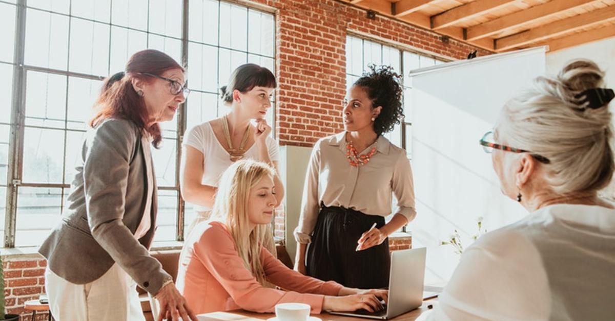 5 mulheres em uma reunião de planejamento de eventos corporativos