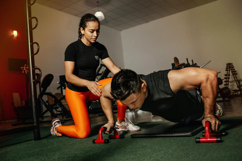 A personal training session in gym held by a personal trainer and a gym lover