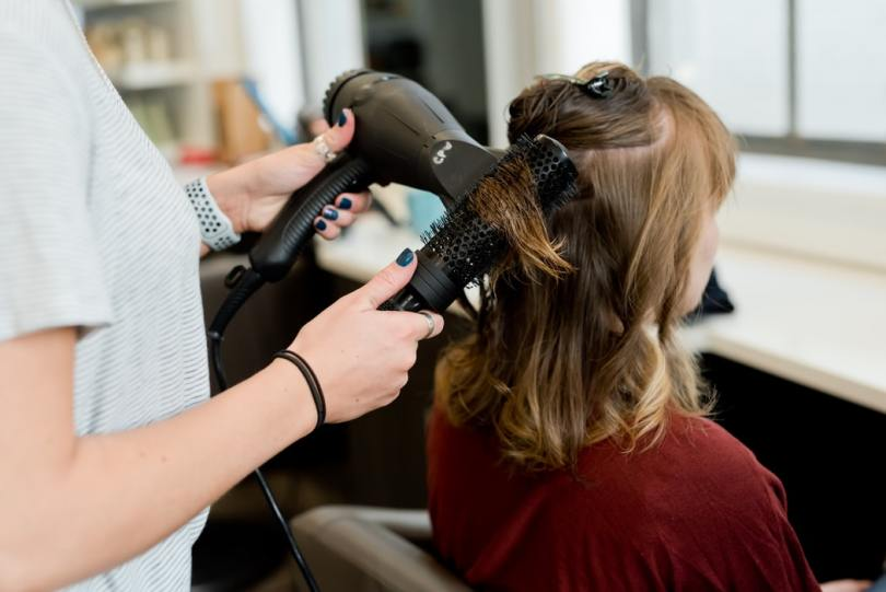 A hair stylist styling customer's hair using a dryer