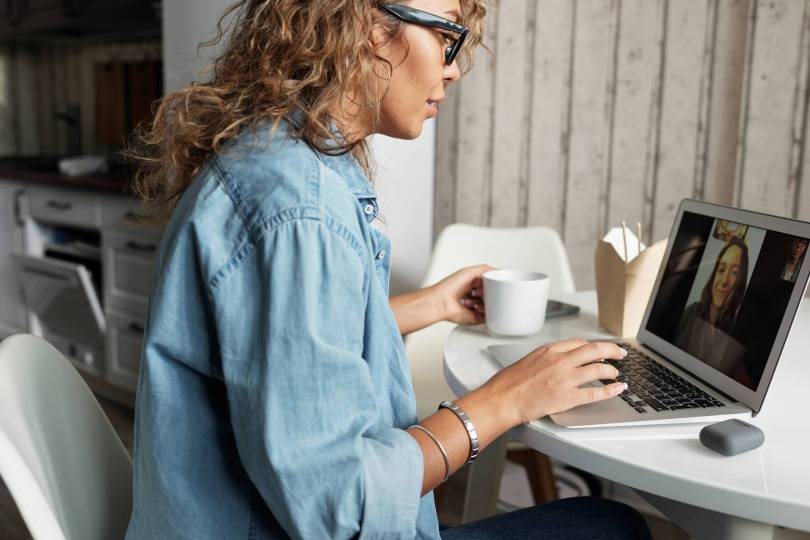 A salon owner providing online consultation to her customer using a laptop