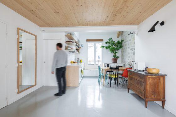 Vue de la cuisine depuis le salon, avec un plafond en bois clair brut