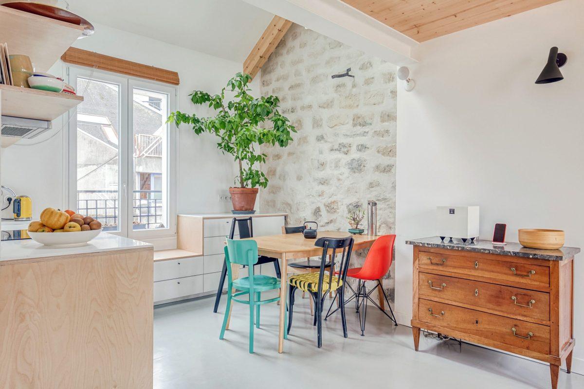 Photo de la cuisine d'architecte, ouverte sur le salon, avec un mur en pierres