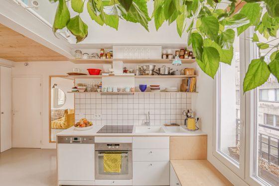 Vue de face de la cuisine, avec un reflet où l'on aperçoit le salon en arrière plan