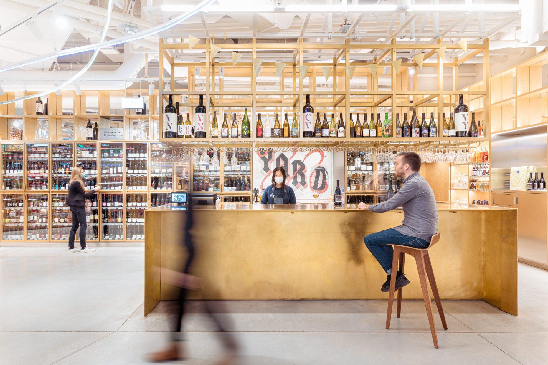 Le plan de travail du bar à vins YARD paris et homme prend un verre