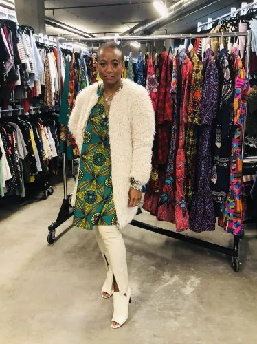 Erika in The Poet Printed Shift (dress) in Green Multi, paired with a cream faux fur coat, cream faux leather leggings, and ankle boots. Style bold prints and bright colors year round!