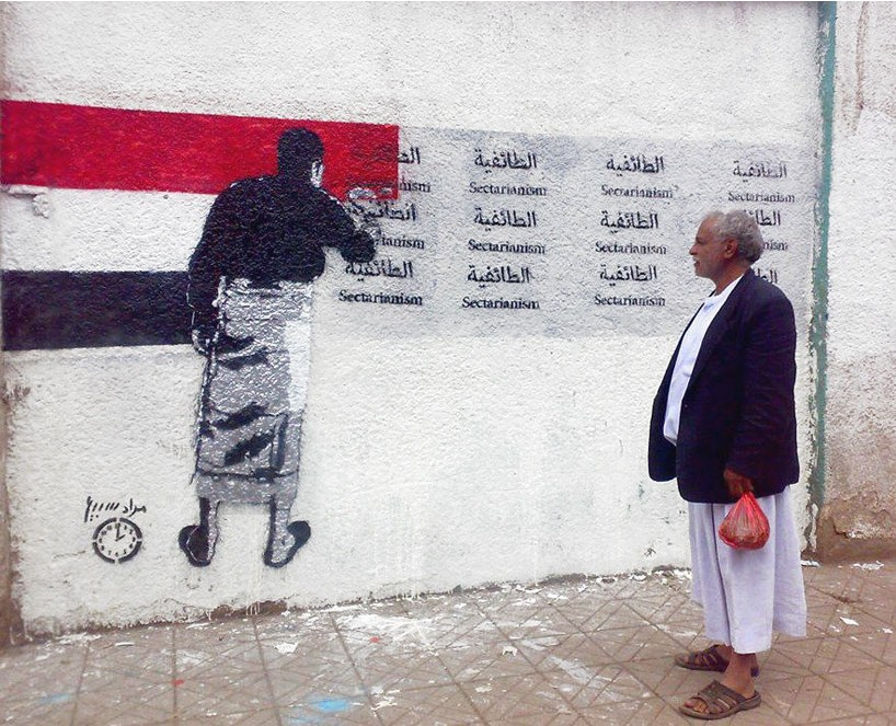 Image from Murad Subay's 3rd. Campaign, 'Sectarianism'.The Yemeni flag being painted over the word for sectarianism. Sana'a, Yemen, 2013