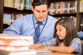 Male teacher assists elementary age girl with homework in school classroom or library setting.