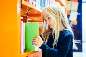 Child girl putting book on shelf