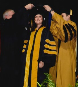 Erin Stauder getting her doctorate in her graduation robes