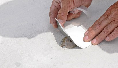 damaged rubber rv roof, picture of a person patching a damaged rubber rv roof
