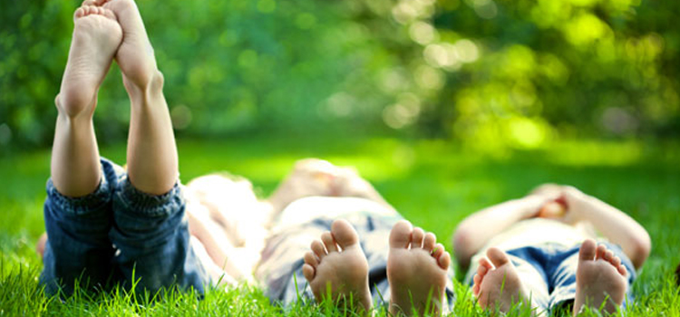 ways to connect with nature, picture of children laying in a field connecting with nature