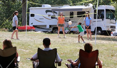 summer holiday rving, picture of 3 people sitting in the shade while the family plays volley ball with rvs in the background, memorial day rv camping