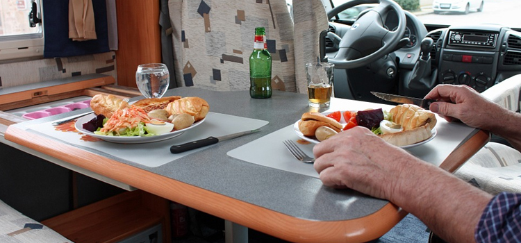 go rving to create lasting memories, picture of a booth dinette inside of a rv with a guy eating dinner, go rving