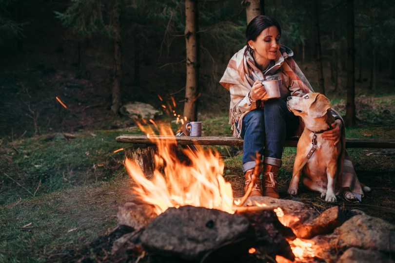 woman and dog by outside fire