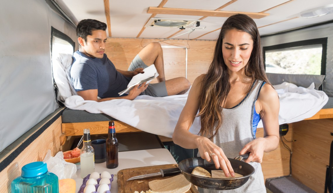 happy couple cooking a meal in their rv kitchen