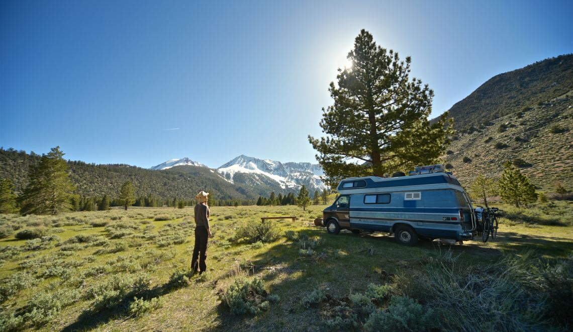 isolated camping spots man looking at his rv in open field with mountains in the background