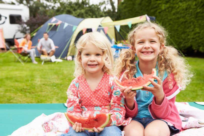 Children Enjoying Picnic Whilst On Family RV Camping Holiday