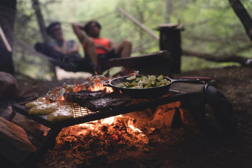 Couple relaxing in a hammock while grilling food at a campsite - RV camping