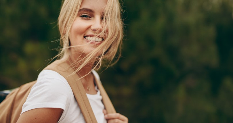 Close up of woman on a holiday walking in a park wearing a bag. Portrait of a smiling woman with brown hair flying over her face. RVing trip concept