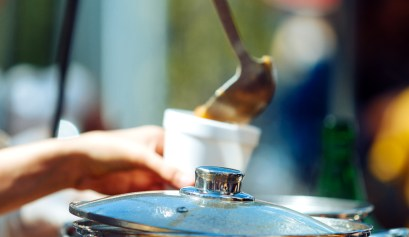Hand of woman serving hot soup next to a pan outdoors at a camping site using gourmet whole food recipes