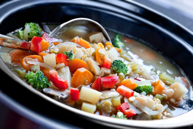 Vegetable soup is a great gourmet food recipes shown here slow-cooked in a crock pot, ready to serve.