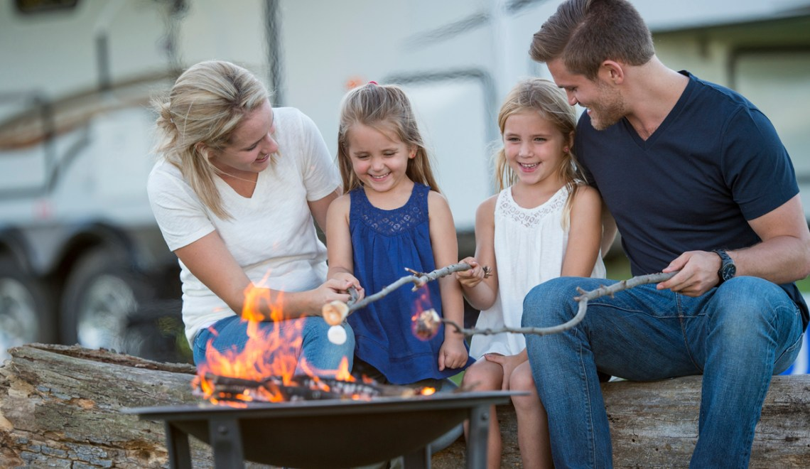Tips for Camping With Your Kids concept. A family of four are roasting marshmallows together around a campfire while on vacation. Their RV is parcked in the background of the picture.