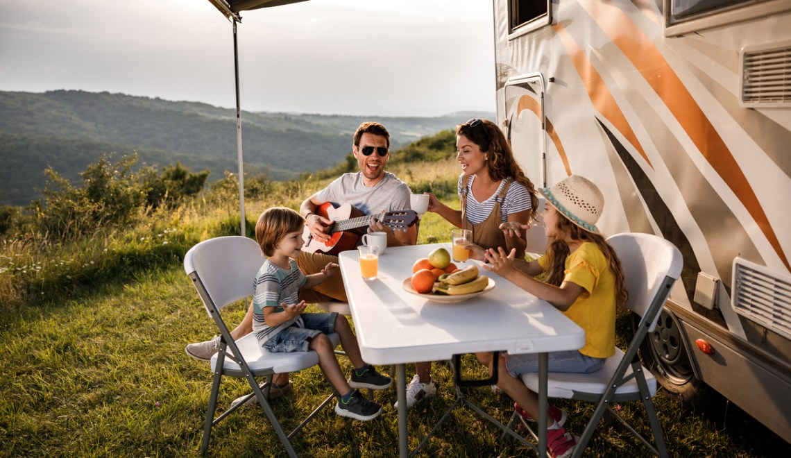 A family sitting, singing, bonding, and camping outside of their RV trailer.