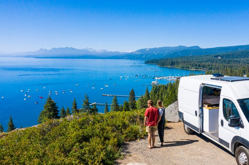 Couple with a parked RV enjoying the sight of nature and viewpoint of a lake.