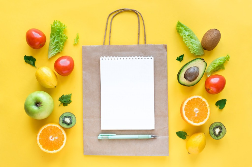Grocery bag and clipboard with vegetable garden layout