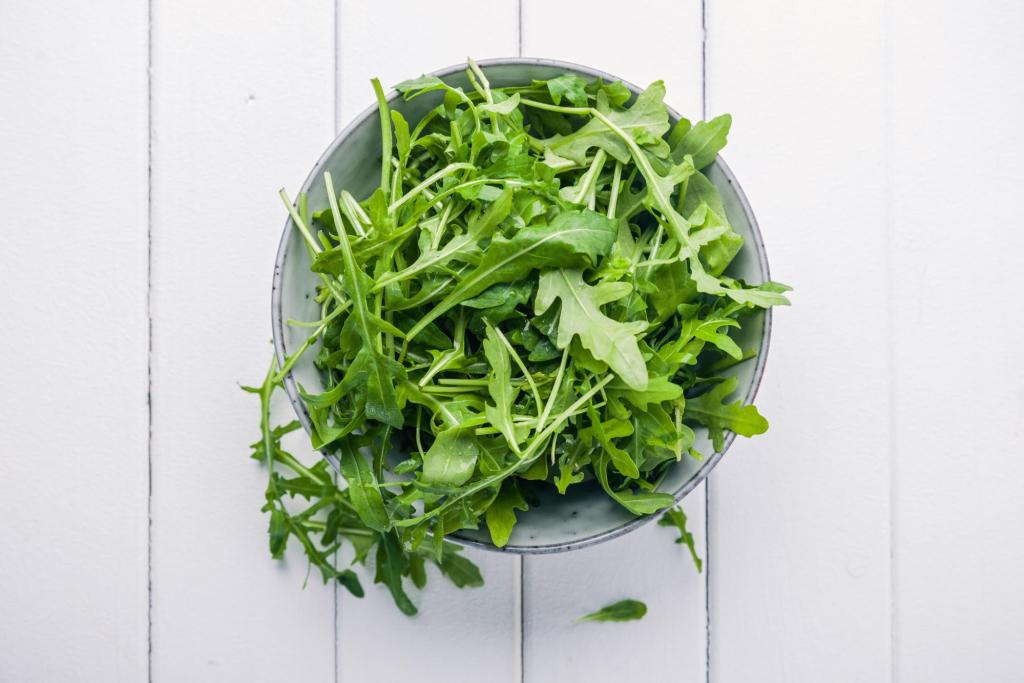 A bowl of arugula on top of a white wooden surface