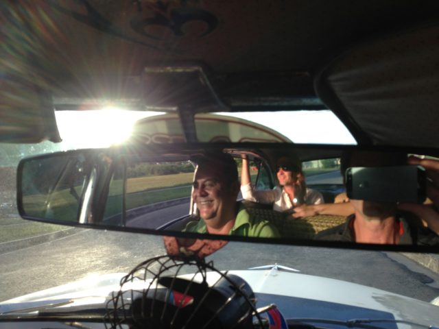Smiling driver seen in rear view mirror of antique car in Cuba
