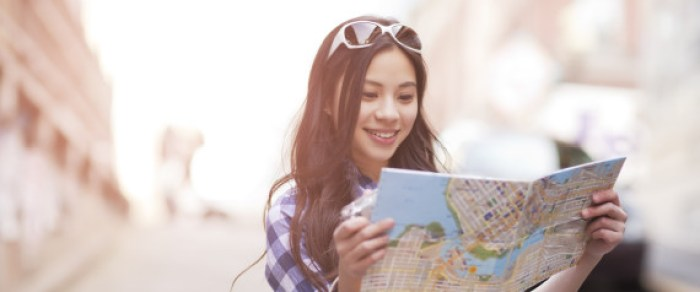 A pretty woman with glasses on her head reads a map