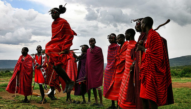 Masai dance. Men looking at another man who is jumping.