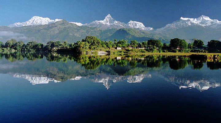 A lake and mountains topped with snow, pokhara