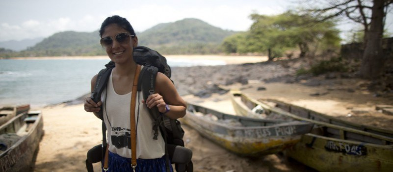 A smiling woman backpacker on a beach
