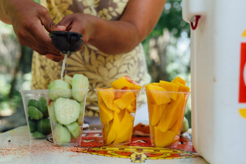 A woman putting lime of fresh fruits and vegetables