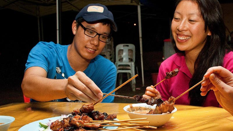 Two people eating chicken satay skewers
