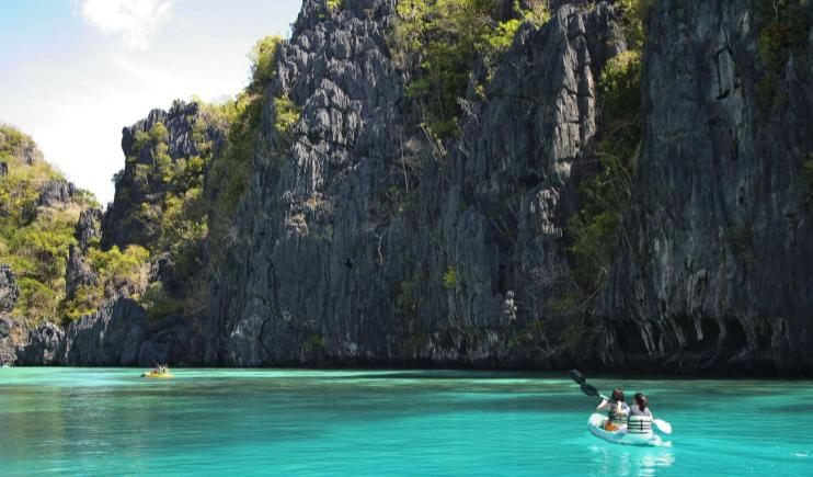 Travellers kayaking through a blue lagoon- Philippines Travel Tips