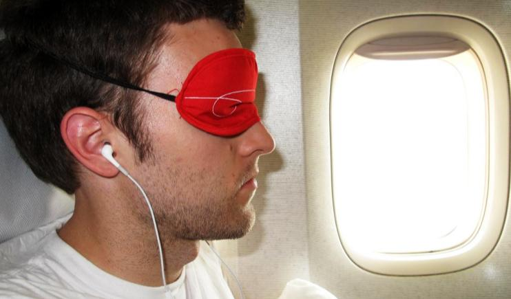 Zone out with an eye mask and earphones- Long Haul Flight Tips