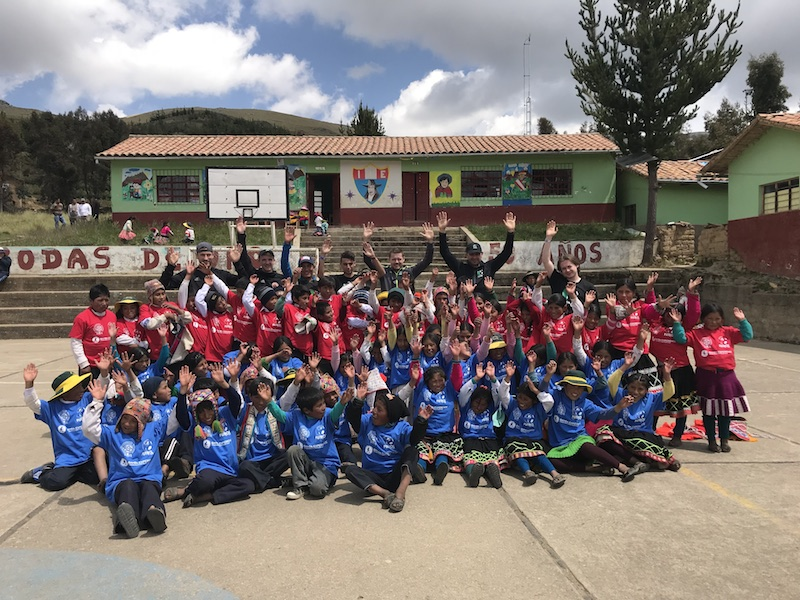 A group of Children and Fotbol for Kids Volunteers throw their hands up in the air.