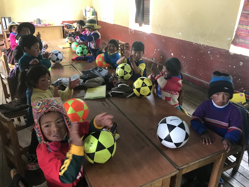 A group of Peruvian children with coloured footballs in a classroom