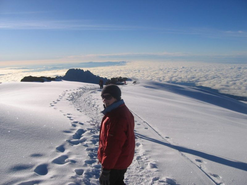 Woman in red jacket standing in snow on Mount Kilimanjaro