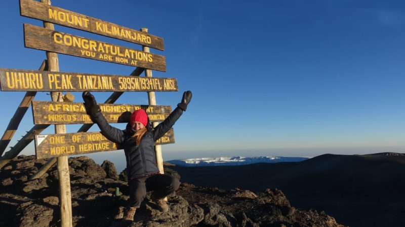 Woman in red beanie at the Uhuru Peak, Mount Kilimanjaro