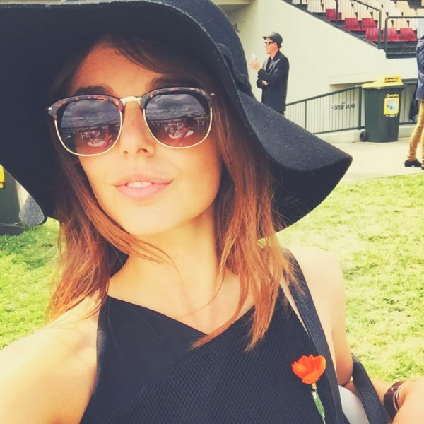 Brunette girl with glasses and a hat dressed in black.