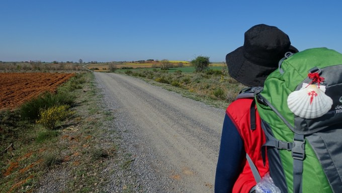 A man with a hat and a backpack walks along a road on The Camino de Santiago