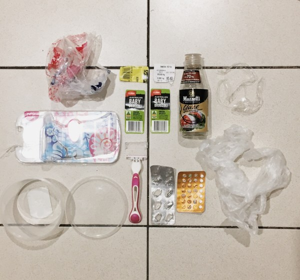 Single use plastic packets and containers on a tiled floor